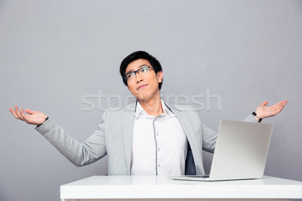 Businessman sitting at the table and shrugging Stock photo © deandrobot