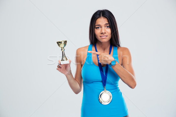 Stock photo: Sports woman pointing finger on the winners cup