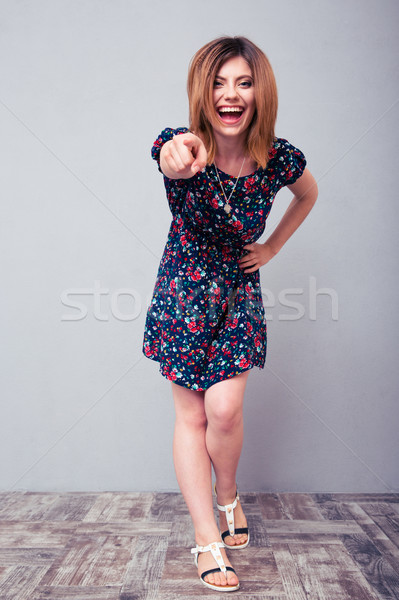 Laughing woman pointing finger at camera Stock photo © deandrobot