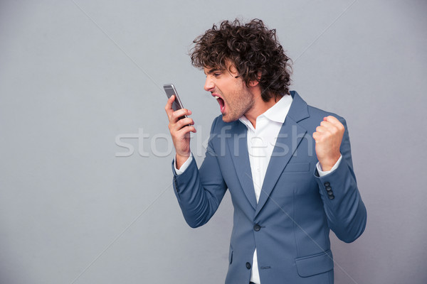 Angry businessman shouting on smartphone Stock photo © deandrobot