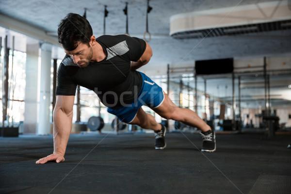 Athlet doing one hand push-ups Stock photo © deandrobot