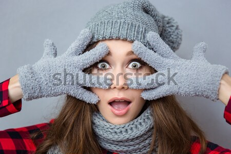 Woman looking at the camera through magnifying glass Stock photo © deandrobot