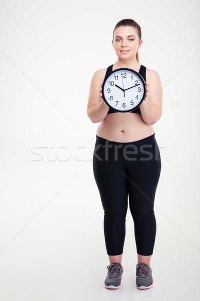 Mosolyog kövér nő tart fal óra Stock fotó © deandrobot