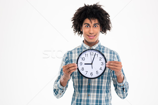 Happy afro american man holding wall clock Stock photo © deandrobot