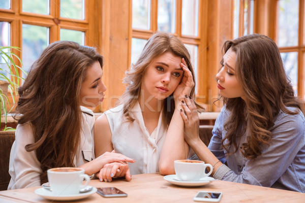 Two women comforting crying girl in cafe  Stock photo © deandrobot