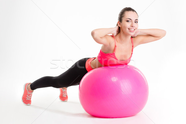 Pretty smiling young sportswoman exercising with fitball  Stock photo © deandrobot