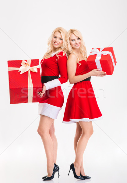 Two sisters twins in santa claus costumes  holding big gifts  Stock photo © deandrobot