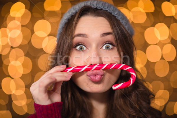 Amusing cute curly girl making funny face using candy cane  Stock photo © deandrobot