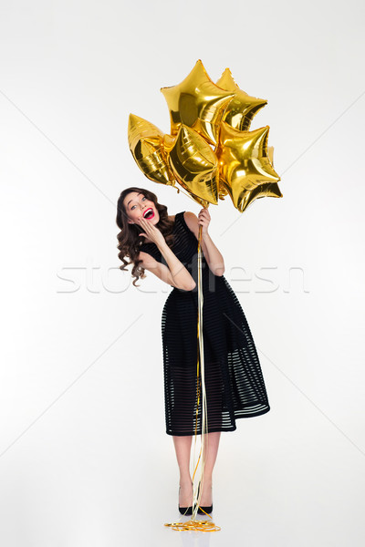 Amusing cheerful lovely curly girl  holding golden balloons Stock photo © deandrobot