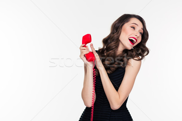 Happy attractive woman with retro hairstyle talking covering phone receiver  Stock photo © deandrobot