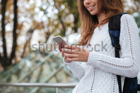 Cheerful beautiful young woman standing and holding blank screen tablet  Stock photo © deandrobot