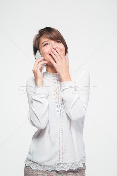 Attractive woman covered mouth with hand and talking on smartphone  Stock photo © deandrobot
