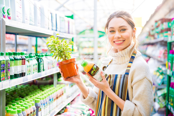Happy woman gardener buying agricultural chemicals for plants  Stock photo © deandrobot