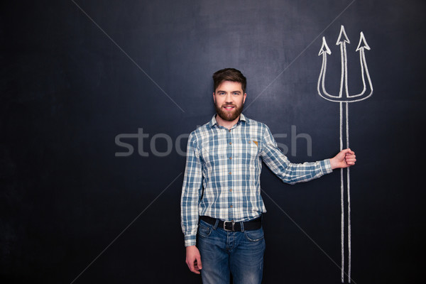 Smiling man holding drawing trident over chalkboard background Stock photo © deandrobot
