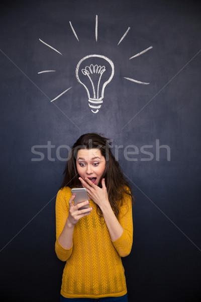 Amazed happy woman using mobile phone over chalkboard background Stock photo © deandrobot