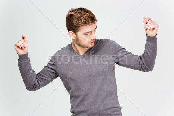 Handsome confident man in grey pullover dancing with raised hands Stock photo © deandrobot