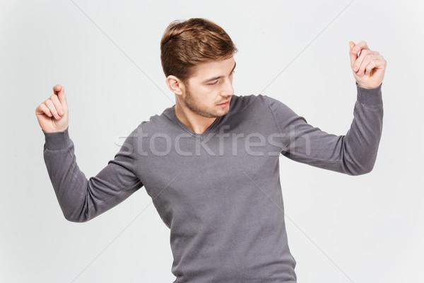 Bello uomo grigio pullover dancing mani alzate Foto d'archivio © deandrobot