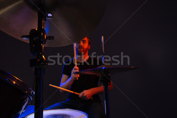 Attractive bearded man drummer with closed eyes enjoying playing drums Stock photo © deandrobot