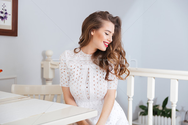 Happy lovely young woman in white dress sitting at cafe  Stock photo © deandrobot