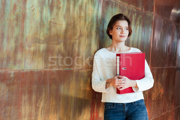 Pensive pretty young woman holding red ring binder folder  Stock photo © deandrobot