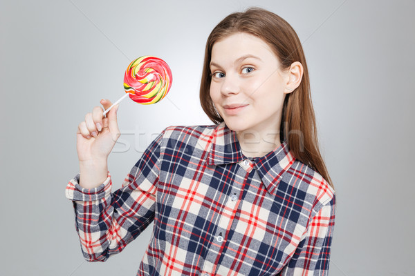 Smiling beautiful teenage girl in checkered shirt holding lollipop  Stock photo © deandrobot