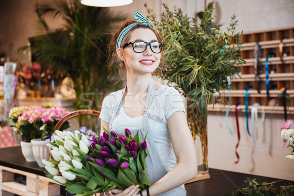 Woman florist holding white and purple tulips in flower shop Stock photo © deandrobot