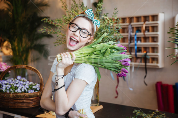 Happy woman florist holding bunch of purple tulips and winking Stock photo © deandrobot