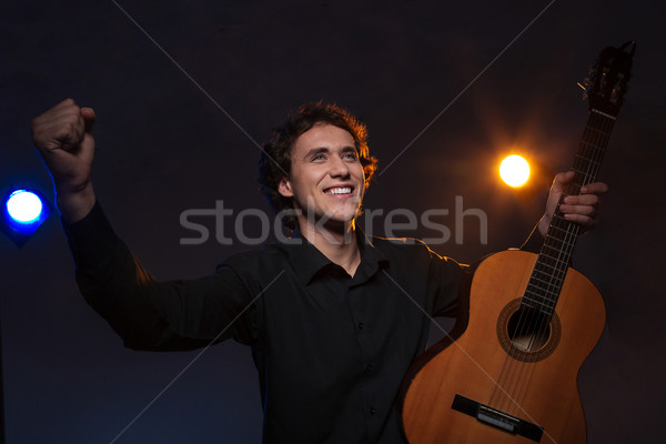 Happy man with a guitar gets applause Stock photo © deandrobot