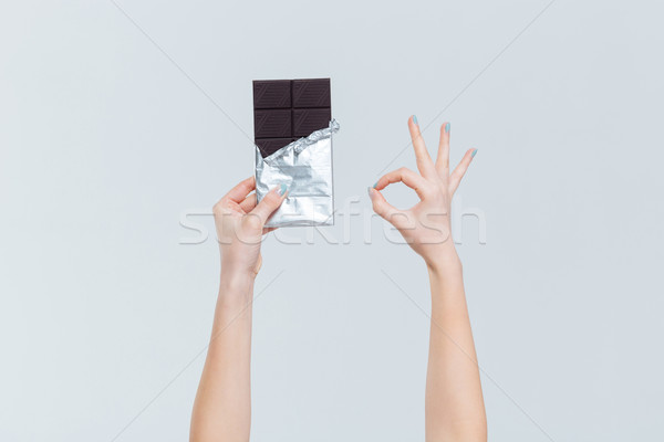 Stock photo: Female hands holding chocolate and showing ok sign