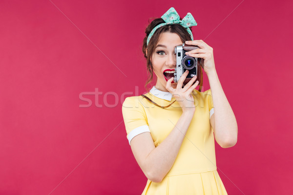 Happy beautiful pinup girl taking photos using vintage camera Stock photo © deandrobot