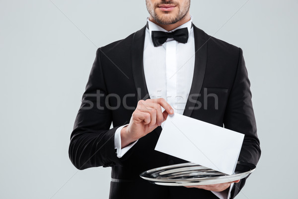 Waiter in tuxedo with bowtie holding blank card on tray Stock photo © deandrobot