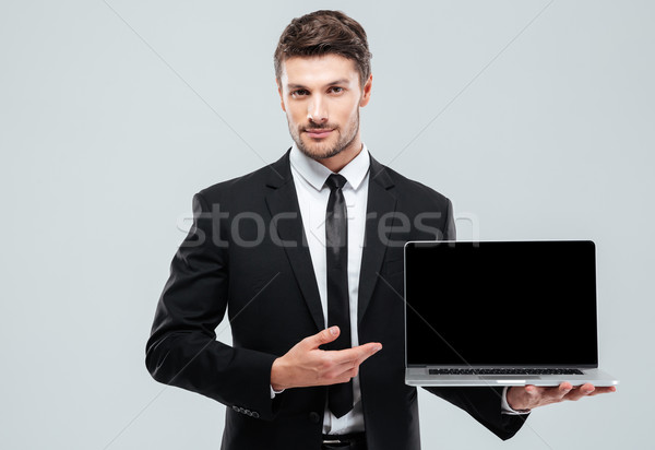 Handsome young businessman showing blank screen laptop Stock photo © deandrobot