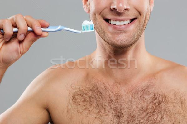 Derűs férfi takarítás fogak fogkefe fogkrém Stock fotó © deandrobot
