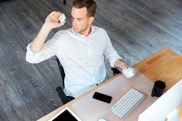Serious businessman throwing crumpled paper and working in office Stock photo © deandrobot