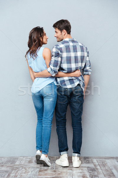 Young happy couple standing backwards over gray background Stock photo © deandrobot