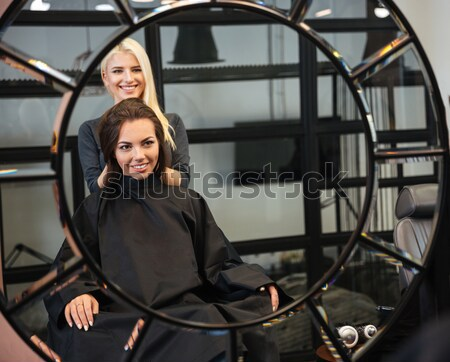 Beautiful blonde female hairdresser holding scissors and comb Stock photo © deandrobot