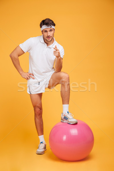 Young handsome sportsman with fitness ball pointing at camera Stock photo © deandrobot