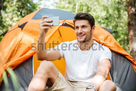Handsome man tourist sitting and drinking from flask in forest Stock photo © deandrobot