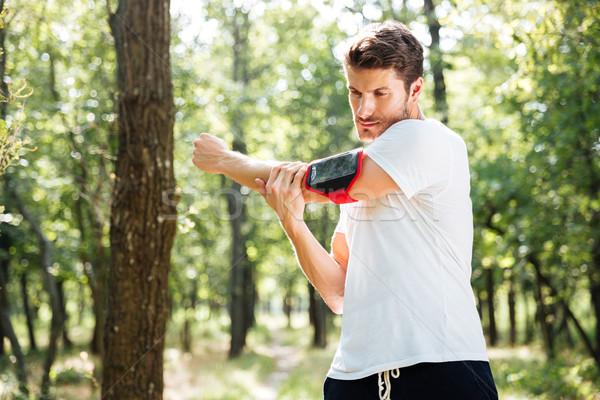 Sportowiec stałego lasu młodych telefonu komórkowego Zdjęcia stock © deandrobot