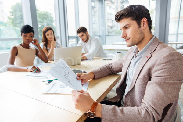 Businessman sitting and creating presentation with business team in office Stock photo © deandrobot