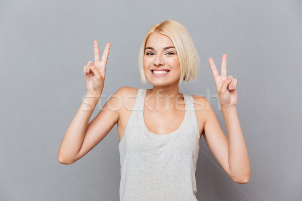 Cheerful cute young woman showing peace sign with both hands Stock photo © deandrobot
