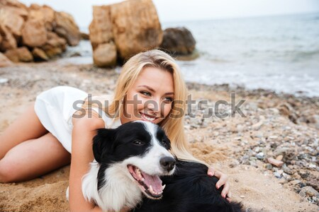 Smiling woman taking selfie with her dog on the beach Stock photo © deandrobot