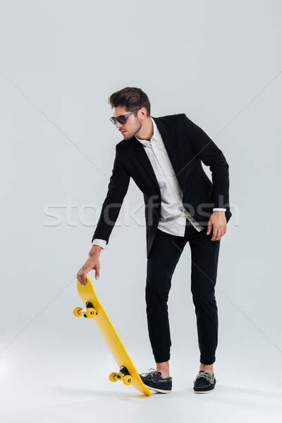 Businessman in sunglasses and suit going to ride a skateboard Stock photo © deandrobot
