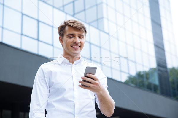 Smiling young businessman using mobile phone near business center Stock photo © deandrobot