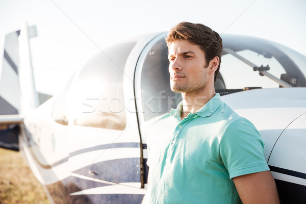 Serious attractive young man near small airplane Stock photo © deandrobot