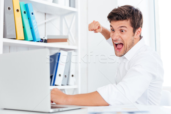 Stressed angry businessman hitting laptop with fist Stock photo © deandrobot
