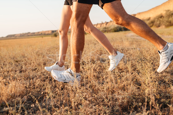 Cropped image of a young couple legs in sneakers running Stock photo © deandrobot