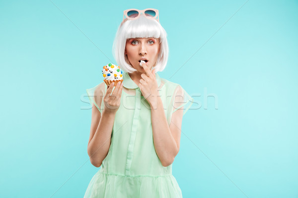 Pretty blonde young woman standing and tasting cupcake by finger Stock photo © deandrobot
