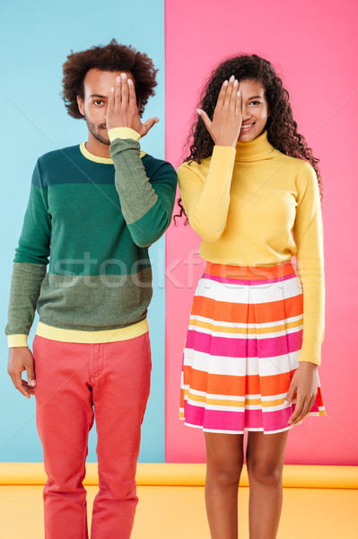 Smiling young couple covered halves of their faces by hands Stock photo © deandrobot