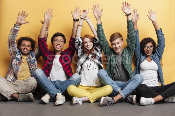 Grupo pessoas felizes sessão juntos as mãos levantadas Foto stock © deandrobot